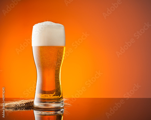Foto op Plexiglas Bier / Cider Glass of beer with orange background