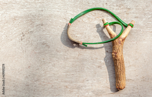 Photo  The old slingshot on old wood background.