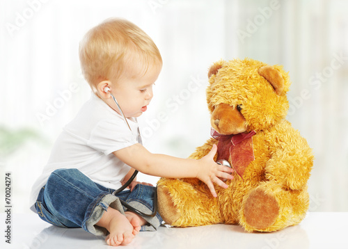 baby plays in doctor toy teddy bear and stethoscope #70024274