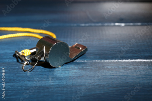 Cuadros en Lienzo  Sport metal whistle on color wooden background