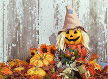Cute Scarecrow Surrounded By Autumn Decorations