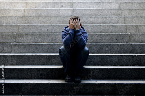 Young homeless man sad crying in depression on ground street Wallpaper Mural