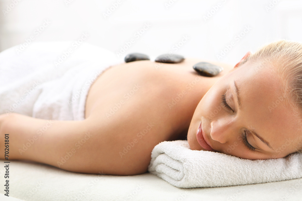 Fototapeta Masaż gorącymi kamieniami, kobieta w salonie spa