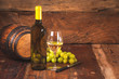 Glass of white wine with bottle and barrel on a rustic wooden ta