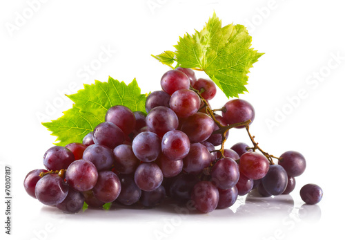 Fototapeta Bunch of ripe red grapes with leaves isolated on white