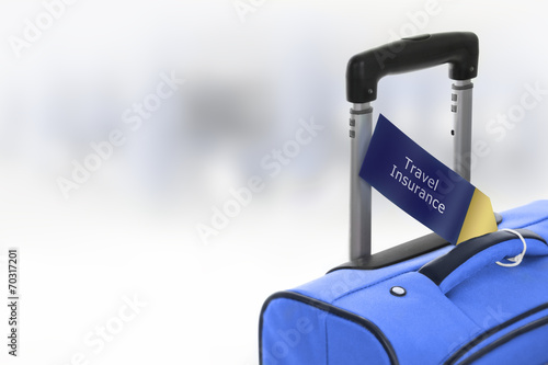 Fotografija  Travel Insurance. Blue suitcase with label at airport.
