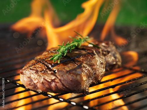 Fototapeta  steak with flames on grill with rosemary