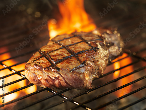 beef steak cooking over flaming grill Canvas Print