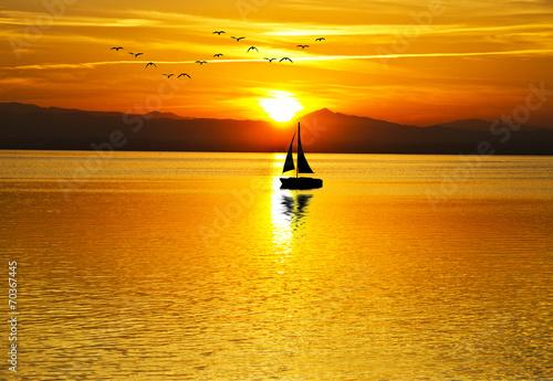 velero surcando el mar en el amanecer