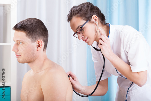 Photo Doctor auscultating patient