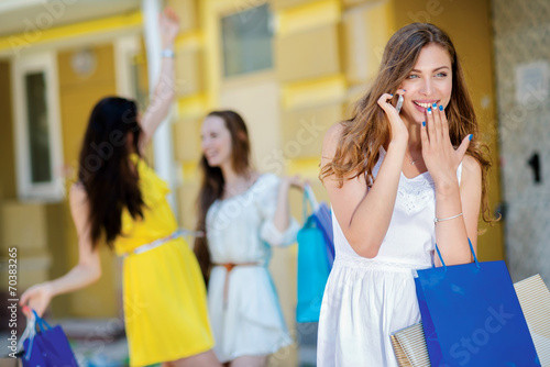 Photo Great news while shopping. Young and pretty girls is talking on