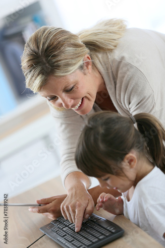 Fototapeta Teacher with little girl in class using computer and tablet obraz na płótnie