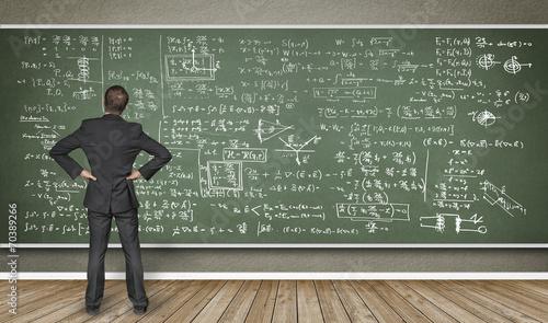 Mann steht vor Wandtafel mit vielen Formeln Fototapete