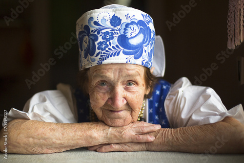 Obraz na płótnie Old woman in traditional folk costume in  his house.