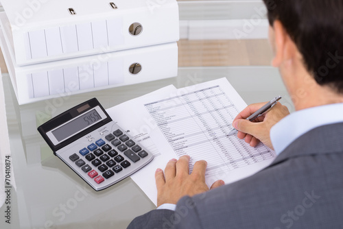 Male accountant calculating invoices Wallpaper Mural