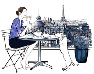 Woman having breakfast on a balcony in Paris