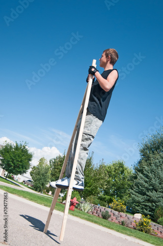 Fotografie, Tablou  Teenage boy on stilts