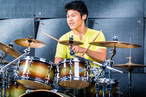 Photo Asian musician drummer in recording studio