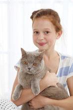 Beautiful Little Girl With Cat On Light Background