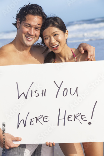 Photo  Asian Couple at Beach Wish You Were Here Sign