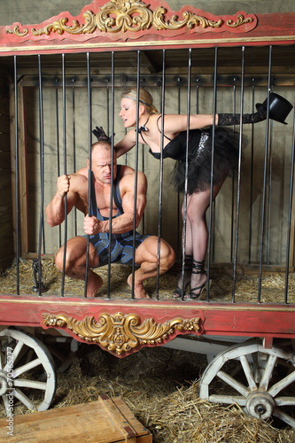 Photo  Beautiful girl calms furious athlete in cage for animals