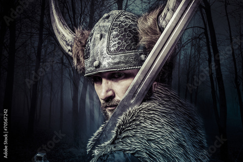 Fotografie, Obraz  Sword, Viking warrior with helmet over forest background