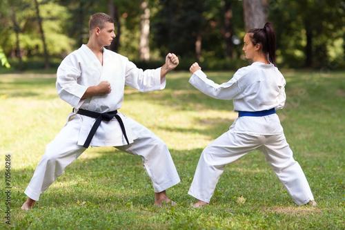 Staande foto Vechtsport oman doing Gyaku-tsuki exercise with her instructor
