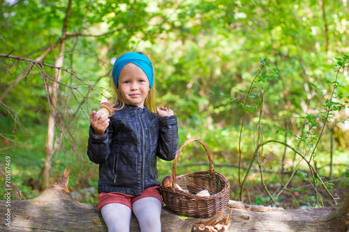 Stampe  Little girl gathering mushrooms in an autumn forest