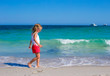 Adorable little girl playing in shallow water at white beach