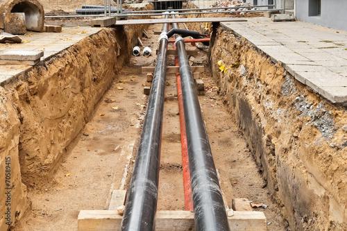 Fotografia  Neue und alte Fernwärmerohre in einer Baugrube