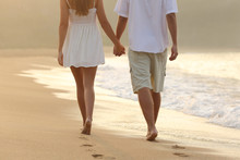 Couple Taking A Walk Holding Hands On The Beach