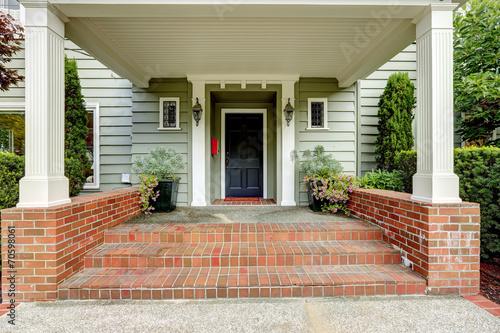 Fototapeta Large entrance porch with columns and brick trim