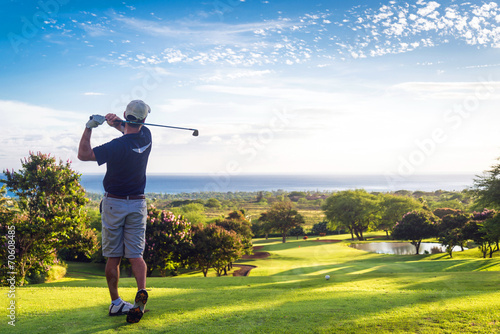 Spoed Foto op Canvas Golf Man hitting golf ball down hill towards ocean and horizon
