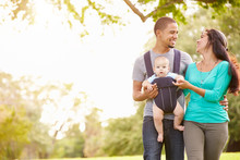Family With Baby Son In Carrier Walking Through Park