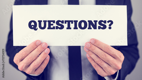 Businessman holding Questions sign towards you Wallpaper Mural