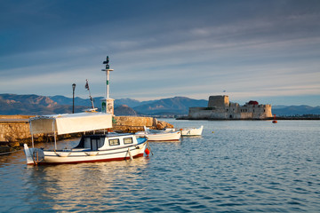 Fishing boats in Nafplio harbour and Bourtzi castle, Greece.