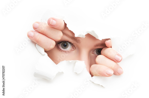 Fotografía  eyes of woman peeking through a  hole torn in white paper poster