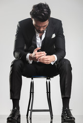 mężczyzna w smokingu patrząc w dół siedząc na stołku,