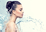 Beautiful model woman with splashes of water in her hands