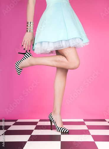 Fotografia  Young woman standing on one leg wearing high heels