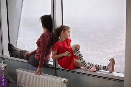 Fotografie, Obraz  Woman and young girl sitting on the windowsill