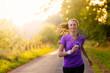 canvas print picture - Sportliche Frau hört Musik beim Jogging
