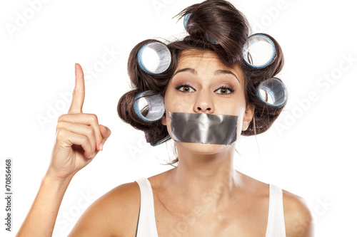 Fototapety, obrazy: Housewife with adhesive tape over her mouth with finger up