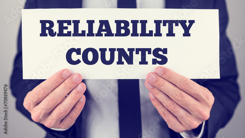 Man Holding Sign Reading Reliability Counts Canvas Print