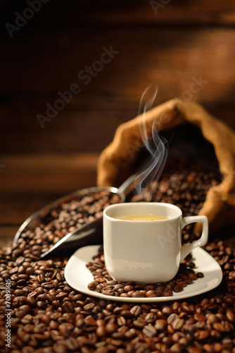 Wall Murals Cafe Coffee cup with smoke and coffee beans on old wooden table