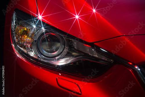 Hood and headlights of sport red car with silver stars