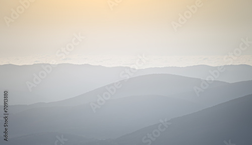 Tuinposter Lichtroze Silhouettes of mountain slopes in the haze