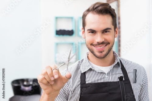 Handsome hair stylist holding scissors