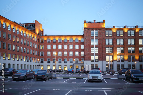 Car parking in courtyard of building built of red bricks