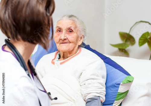 Fotografia  young nurse caregiving an old lady lying in bed